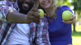 Το χαμόγελο ανάμιξε το ζεύγος φυλών που παρουσιάζει πράσινα μήλα, υγιής έννοια διατροφής, διατροφή φιλμ μικρού μήκους