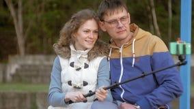 Το χαμόγελο ανδρών και γυναικών παίρνει τη μόνη εικόνα selfie με το έξυπνο τηλέφωνο κινητό στο πάρκο φιλμ μικρού μήκους