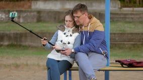 Το χαμόγελο γυναικών ανδρών fnd παίρνει τη μόνη εικόνα selfie με το έξυπνο τηλέφωνο κινητό στο πάρκο απόθεμα βίντεο