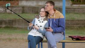 Το χαμόγελο γυναικών ανδρών fnd παίρνει τη μόνη εικόνα selfie με το έξυπνο τηλέφωνο κινητό στο πάρκο φιλμ μικρού μήκους