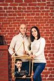 Το χαμόγελο πατέρων και μητέρων, και γιος τιτιβίζει από το αυτοσχεδιασμένο σπίτι στο στούντιο ενάντια στο σκηνικό του τουβλότοιχο στοκ φωτογραφία
