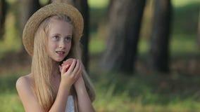 Το χαμόγελο χαριτωμένο το κορίτσι που τρώει το εύγευστο ροδάκινο υπαίθρια απόθεμα βίντεο