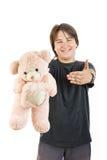 Το χαμόγελο αγοριών και το κράτημα teddy αντέχουν το παιχνίδι ως δώρο Στοκ Εικόνες