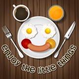 Το χαμόγελο αντέχει κάνει με τα τηγανισμένο αυγά και το λουκάνικο και το ποτό Στοκ Εικόνες