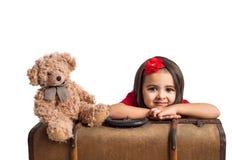 Το χαμόγελο μικρών κοριτσιών με τη βαλίτσα και το παιχνίδι αντέχουν Στοκ εικόνα με δικαίωμα ελεύθερης χρήσης