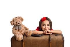 Το χαμόγελο μικρών κοριτσιών με τη βαλίτσα και το παιχνίδι αντέχουν Στοκ Εικόνες