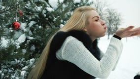 Το χαμόγελο του φυσώντας χιονιού γυναικών από παραδίδει τον παγωμένο χειμώνα στο πεύκο fores απόθεμα βίντεο
