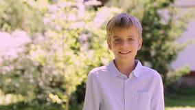 Το χαμόγελο το αγόρι υπαίθρια στο θερινό κήπο φιλμ μικρού μήκους