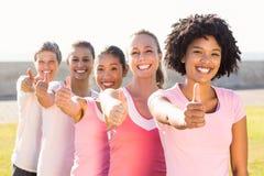 Το χαμόγελο των γυναικών που φορούν το ροζ για το καρκίνο του μαστού και που κάνουν φυλλομετρεί επάνω Στοκ φωτογραφία με δικαίωμα ελεύθερης χρήσης