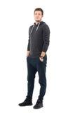 Το χαμόγελο χαλάρωσε το νέο αθλητικό άτομο στη με κουκούλα μπλούζα με παραδίδει τις τσέπες Στοκ Εικόνα
