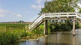 Το χαρακτηριστικό ολλανδικό τοπίο με μια παλαιά ξύλινη γέφυρα και σύγχρονος κερδίζει στοκ εικόνα