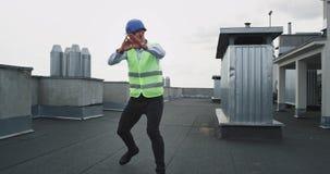 Το χαρισματικό άτομο με ένα κράνος στο χορεύοντας νέο μηχανικό εργοτάξιων οικοδομής με ένα συναίσθημα γενειάδων διέγειρε στην κορ φιλμ μικρού μήκους