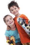 Το χαριτωμένα αγόρι και το κορίτσι είναι skateboards φροντίδας Στοκ Εικόνα