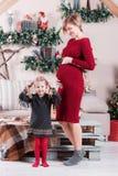 Το χαριτωμένες έγκυες mom και η κόρη στέκονται κοντά στο όμορφο διακοσμημένο χριστουγεννιάτικο δέντρο στο σπίτι, εξετάζοντας τη κ Στοκ φωτογραφία με δικαίωμα ελεύθερης χρήσης