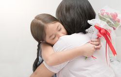 Το χαριτωμένο αγκάλιασμα κοριτσιών και δίνει τα rosees λουλουδιών της, στοκ εικόνες