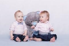 Το χαριτωμένο αγοράκι και το λατρευτό μικρό κορίτσι με μεγάλο έναν teddy αντέχουν Στοκ Εικόνες