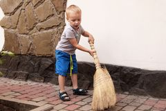 Το χαριτωμένο αγοράκι σκουπίζει το ναυπηγείο με μια σκούπα, βοηθός μητέρων στοκ φωτογραφίες με δικαίωμα ελεύθερης χρήσης