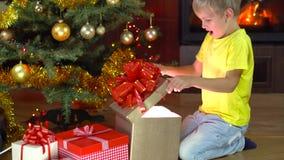 Το χαριτωμένο αγόρι ανοίγει το παρόν του στο χριστουγεννιάτικο δέντρο απόθεμα βίντεο