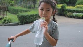 Το χαριτωμένο ασιατικό πόσιμο νερό μικρών κοριτσιών στο πάρκο με το χαμόγελο και την παρουσίαση ευτυχίας φυλλομετρεί επάνω απόθεμα βίντεο