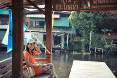 Το χαριτωμένο ασιατικό ταϊλανδικό κορίτσι τον χαλαρώνει στο περίπτερο πλησίον riversi Στοκ Φωτογραφία