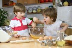 Το χαριτωμένο γλείψιμο αγοριών χτυπά ελαφρά ενώ ο δίδυμος αδερφός του που αναμιγνύει τα αυγά στη μίξη του κύπελλου στην κουζίνα Στοκ Εικόνες