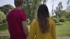 Το χαριτωμένο ευτυχές ερωτευμένο περπάτημα ζευγών στο πράσινο πάρκο κοντά στην όμορφη λίμνη που κρατά ήπια κάθε άλλων παραδίδει τ απόθεμα βίντεο