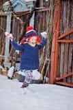 Το χαριτωμένο ευτυχές κορίτσι παιδιών που έχει τη διασκέδαση και που ρίχνει το χιόνι μέσα Στοκ Φωτογραφία