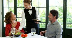 Το χαριτωμένο ζεύγος περιμένουν σε ένα γυαλί κατά τη διάρκεια της συνεδρίασης του μεσημεριανού γεύματος απόθεμα βίντεο
