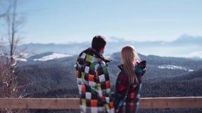 Το χαριτωμένο ζεύγος στο πολύχρωμο σκι ταιριάζει τη στάση στη γέφυρα παρατήρησης και το κοίταγμα στα πανέμορφα βουνά ρομαντικός απόθεμα βίντεο