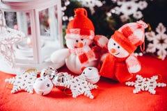 Το χαριτωμένο ζεύγος των μικρών χιονανθρώπων στέκεται κοντά στο άσπρο φανάρι νεράιδων με μια καρδιά παιχνιδιών σε το και το διακο Στοκ εικόνες με δικαίωμα ελεύθερης χρήσης