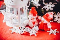 Το χαριτωμένο ζεύγος των μικρών χιονανθρώπων στέκεται κοντά στο άσπρο φανάρι νεράιδων με μια καρδιά παιχνιδιών σε το και το διακο Στοκ εικόνα με δικαίωμα ελεύθερης χρήσης
