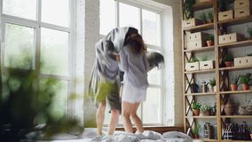 Το χαριτωμένο ζεύγος χορεύει στο κρεβάτι με το κάλυμμα που πηδά και που γελά μαζί έχοντας τη διασκέδαση στο πρωί Σαββατοκύριακου  απόθεμα βίντεο