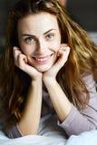 Το χαριτωμένο και όμορφο κορίτσι στην κρεβατοκάμαρα εξετάζει τη κάμερα Στοκ Φωτογραφία