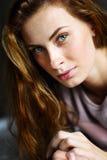 Το χαριτωμένο και όμορφο κορίτσι στο κρεβάτι εξετάζει τη κάμερα Στοκ Εικόνες