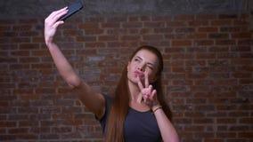 Το χαριτωμένο καυκάσιο θηλυκό παίρνει selfie και παρουσιάζει δύο δάχτυλά της στο τηλέφωνό της στεμένος στο υπόβαθρο τούβλου φιλμ μικρού μήκους