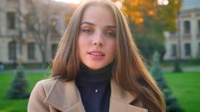 Το χαριτωμένο καυκάσιο θηλυκό στέκεται ήρεμα και εξετάζει την ψύχρα και τη ρίψη καμερών στο αστικό υπόβαθρο στα sunlights υπαίθρι απόθεμα βίντεο