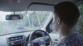 Το χαριτωμένο καυκάσιο κοντό μαλλιαρό άτομο οδηγεί το δεξί αυτοκίνητο κίνησης στον αγροτικό δρόμο απόθεμα βίντεο