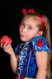 Το χαριτωμένο κορίτσι έντυσε ως λευκός σαν το χιόνι τρώγοντας ένα μήλο Στοκ Εικόνες