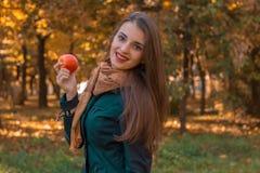 Το χαριτωμένο κορίτσι αξίζει λοξά τα χαμόγελα και κρατά τη Apple στο πάρκο Στοκ Εικόνα