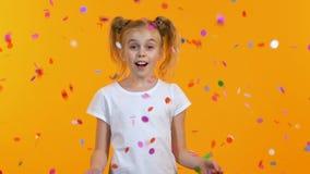 Το χαριτωμένο κορίτσι είναι έκπληκτο να δει πέφτοντας από το κομφετί ουρανού, εορτασμός, παιδική ηλικία φιλμ μικρού μήκους