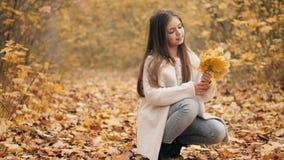 Το χαριτωμένο κορίτσι εφήβων συλλέγει μια ανθοδέσμη των φύλλων φθινοπώρου φιλμ μικρού μήκους