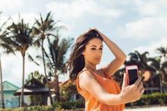 Το χαριτωμένο κορίτσι κάνει selfie στην τροπική παραλία Στοκ Εικόνες