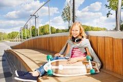 Το χαριτωμένο κορίτσι κρατά skateboard που φορά τα ακουστικά Στοκ φωτογραφίες με δικαίωμα ελεύθερης χρήσης