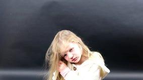 Το χαριτωμένο κορίτσι κτενίζει την τρίχα της Το μικρό κορίτσι είναι ντυμένο στο χειμερινό ιματισμό Χαριτωμένο μικρό κορίτσι στο μ φιλμ μικρού μήκους