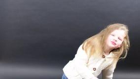 Το χαριτωμένο κορίτσι κτενίζει την τρίχα της Το μικρό κορίτσι είναι ντυμένο στο χειμερινό ιματισμό Χαριτωμένο μικρό κορίτσι στο μ απόθεμα βίντεο