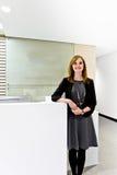 Το χαριτωμένο κορίτσι κλίνει ενάντια στο γραφείο υποδοχής Στοκ Φωτογραφία