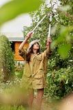 Το χαριτωμένο κορίτσι με μακρυμάλλη κάνει την κοπή με το μεγάλο ψαλίδι κήπων Στοκ Φωτογραφίες