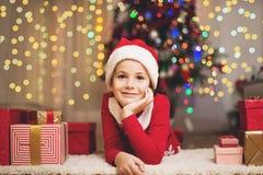 Το χαριτωμένο κορίτσι με παρουσιάζουν και το καπέλο Santa's σε Χριστούγεννα/νέο ένα Year's στοκ εικόνες με δικαίωμα ελεύθερης χρήσης