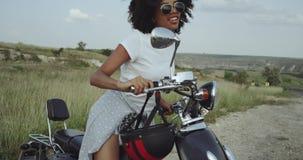 Το χαριτωμένο κορίτσι με την τρίχα Afro προσπαθεί να οδηγήσει μια μοτοσικλέτα ισχίων, που έχει έναν χρόνο διασκέδασης φιλμ μικρού μήκους