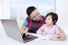 Το χαριτωμένο κορίτσι με τον πατέρα της μαθαίνει να γράφει Στοκ φωτογραφίες με δικαίωμα ελεύθερης χρήσης